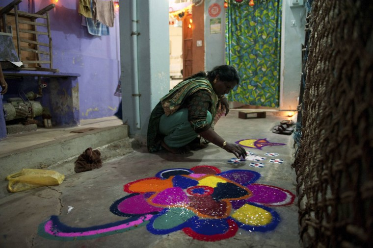 "A member from the Pakistani Hindu community Rasheeda, 32, creates a ""rangoli,"" traditional patterns made from coloured powders, during Diwali celebrations at the Shree Swami Narayan Temple in Karachi, November 3, 2013. Prayers and offerings are made to Hindu deities on Diwali, the annual festival of lights. (Insiya Syed/Reuters)"