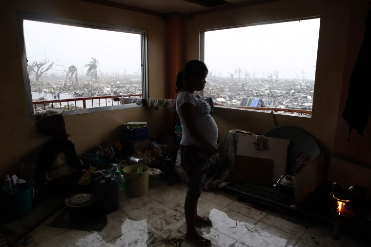 A pregnant woman cooks a meal inside a building overlooking destroyed houses after Super Typhoon Haiyan battered Tacloban city in central Philippines November 10, 2013. One of the most powerful storms ever recorded killed at least 10,000 people in the central Philippines province of Leyte, a senior police official said on Sunday, with coastal towns and the regional capital devastated by huge waves. Super typhoon Haiyan destroyed about 70 to 80 percent of the area in its path as it tore through the province on Friday, said chief superintendent Elmer Soria, a regional police director. (Erik De Castro/Reuters)