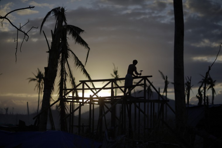 A man is silhouetted as he builds a wooden house in an area destroyed by Typhoon Haiyan, in Palo. Authorities estimate more than 3,900 people were killed when Typhoon Haiyan, one of the largest ever recorded, made landfall in the central Philippines and the sea surged ashore. (John Javellana/Reuters)