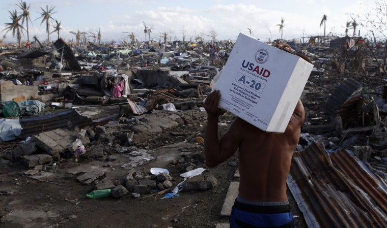 A Typhoon Haiyan victim carries a box of relief goods from the U.S. government, back to his devastated village in Tacloban, central Philippines. (Erik De Castro/Reuters)