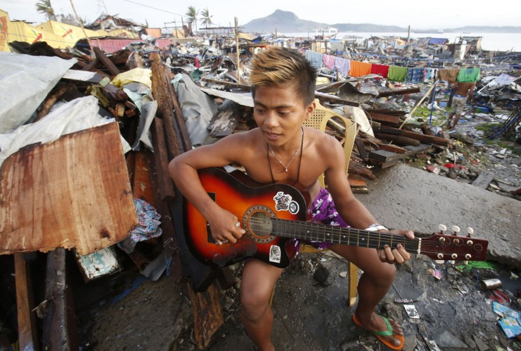 A typhoon survivor plays his guitar outside a makeshift shelter among the ruins of a residential neighbourhood that was devastated by super Typhoon Haiyan two weeks ago in Tacloban city, central Philippines November 22, 2013. (Erik De Castro/REUTERS)