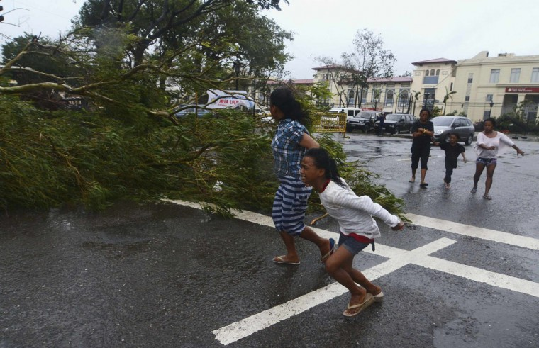 Residents rush to safety past a fallen tree during strong winds brought by Typhoon Haiyan that hit Cebu city, central Philippines Nov. 8, 2013. (Reuters/Zander Casas)