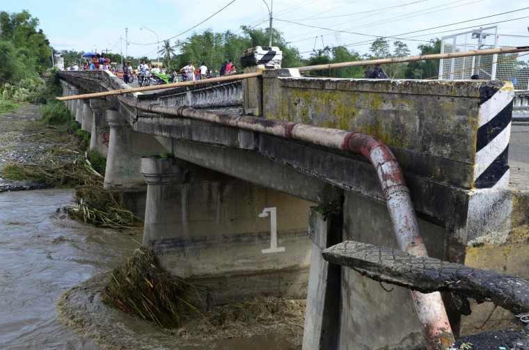 Residents try to cross the damaged Suage bridge after Typhoon Haiyan hit Janiuay, in the Iloilo province in central Philippines November 9, 2013. Typhoon Haiyan, possibly the strongest storm ever to hit land, has devastated the central Philippine city of Tacloban, killing at least 100 people and destroying most houses in a surge of flood water and high winds, officials said on Saturday. The toll of death and damage is expected to rise sharply as rescue workers and soldiers reach areas cut off by the massive storm, now barrelling out of the Philippines towards Vietnam . (Nereo Lujan/REUTERS)