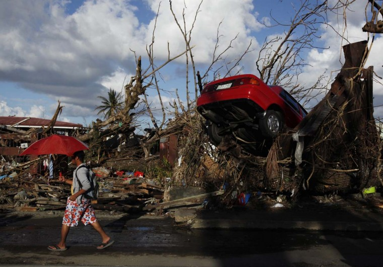 A resident walks past a car which landed amid fallen trees in Tacloban, after super Typhoon Haiyan battered the city in central Philippines, November 18, 2013. The Philippines is facing up to an enormous rebuilding task from Typhoon Haiyan, which killed at least 3,681 people and left 1,186 missing, with many isolated communities yet to receive significant aid despite a massive international relief effort. (Bobby Yip/Reuters)