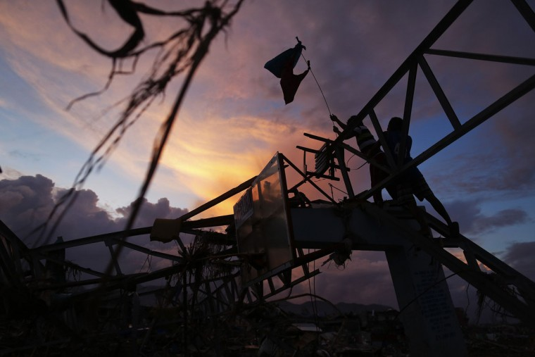Survivors place a makeshift flag over a sports hall destroyed by Typhoon Haiyan, in Tacloban November 20, 2013. The Philippines is facing an enormous rebuilding task from Typhoon Haiyan, which killed at least 3,974 people and left 1,186 missing, with many isolated communities yet to receive significant aid despite a massive international relief effort. (Damir Sagolj/REUTERS)