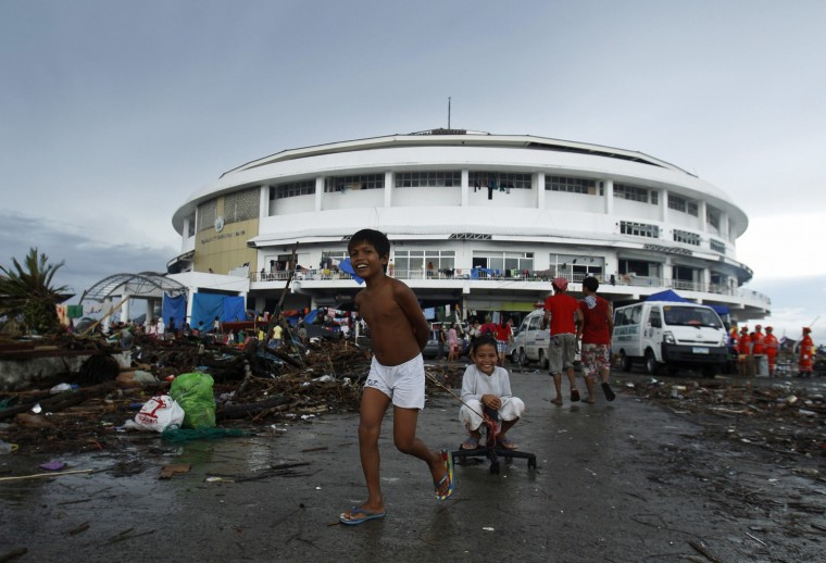 Children play outside the Tacloban City Convention Center, which has become a makeshift refuge center for displaced people after Super Typhoon Haiyan battered Tacloban city in central Philippines November 12, 2013. Philippine officials have been overwhelmed by Super Typhoon Haiyan, one of the strongest on record, which tore through the central Philippines on Friday and flattened Tacloban, coastal capital of Leyte province where officials fear 10,000 people died, many drowning in a tsunami-like wall of seawater. (Edgar Su/REUTERS)