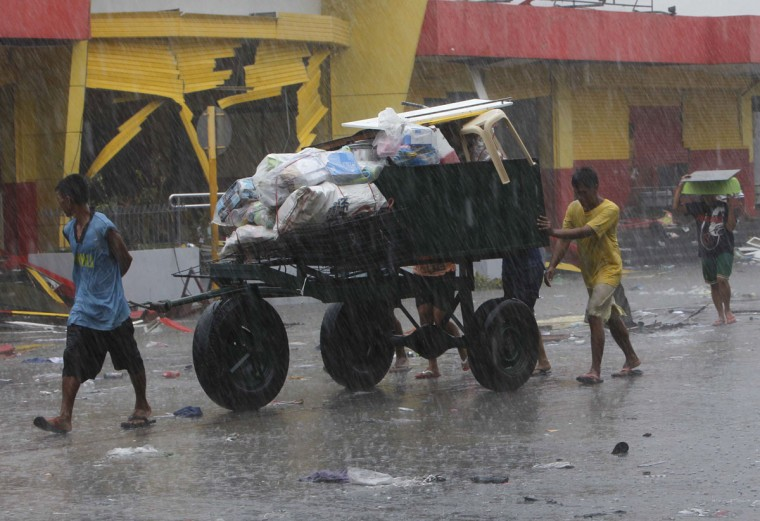 Residents use a cart to transport their belongings after super typhoon Haiyan battered Tacloban city, central Philippines, November 10, 2013. One of the most powerful storms ever recorded killed at least 10,000 people in the central Philippines, a senior police official said on Sunday, with huge waves sweeping away entire coastal villages and devastating the region's main city. (Romeo Ranoco/Reuters)