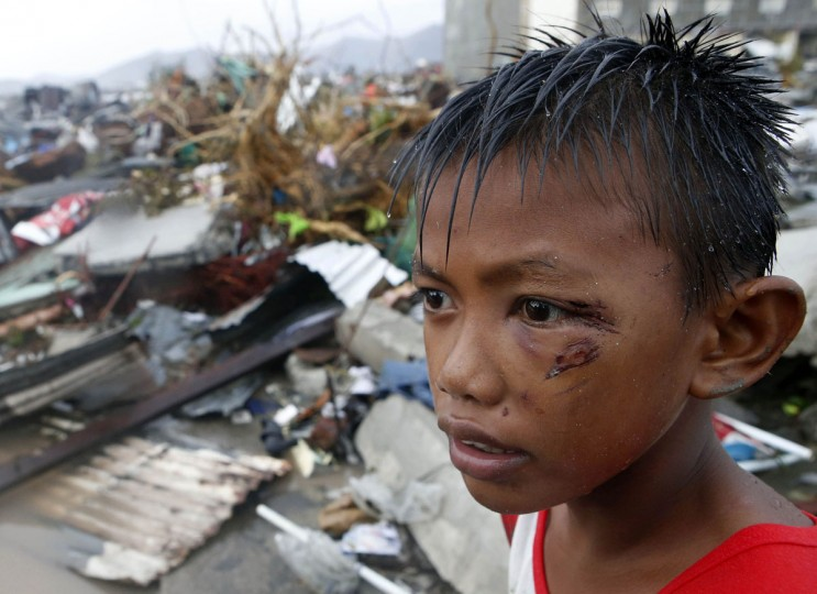 A boy who was wounded by flying debris due to Super Typhoon Haiyan stays at the ruins of his family's house in Tacloban city November 10, 2013. Haiyan, one of the most powerful storms ever recorded killed at least 10,000 people in the central Philippines province of Leyte, a senior police official said on Sunday, with coastal towns and the regional capital devastated by huge waves. (Erik De Castro/Reuters)