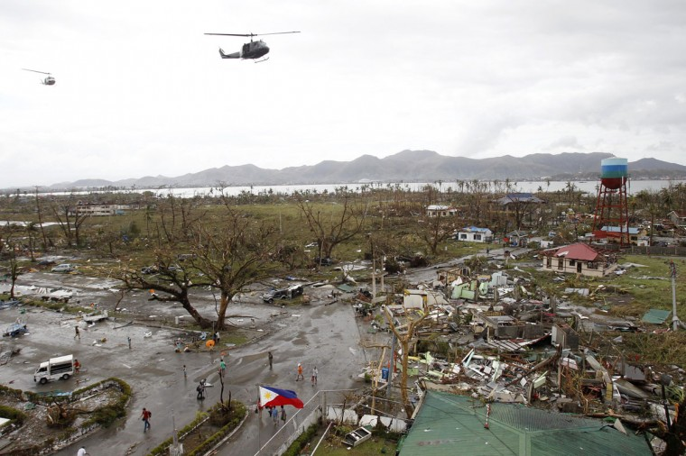 Helicopters hover over the damaged area after super Typhoon Haiyan battered Tacloban city, central Philippines, November 9, 2013. Possibly the strongest typhoon ever to hit land devastated the central Philippine city of Tacloban, killing at least 100 people, turning houses into rubble and leveling the airport in a surge of flood water and high wind, officials said on Saturday. The toll of death and damage from Typhoon Haiyan on Friday is expected to rise sharply as rescue workers and soldiers reach areas cut off by the massive, fast-moving storm which weakened to a category 4 on Saturday. (Romeo Ranoco/REUTERS)