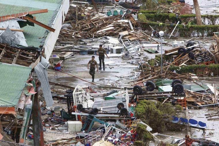 Soldiers walks past the damaged area of an airport after super Typhoon Haiyan battered Tacloban city, central Philippines, November 9, 2013. Possibly the strongest typhoon ever to hit land devastated the central Philippine city of Tacloban, killing at least 100 people, turning houses into rubble and leveling the airport in a surge of flood water and high wind, officials said on Saturday. The toll of death and damage from Typhoon Haiyan on Friday is expected to rise sharply as rescue workers and soldiers reach areas cut off by the massive, fast-moving storm which weakened to a category 4 on Saturday. (Romeo Ranoco/REUTERS)