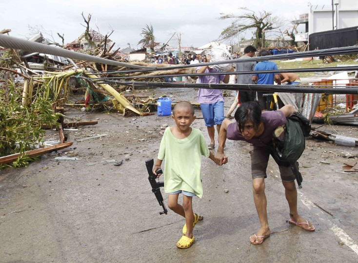 A mother and her son walk under damaged electric cables after super Typhoon Haiyan battered Tacloban city, central Philippines November 9, 2013. Typhoon Haiyan, the strongest typhoon in the world this year and possibly the most powerful ever to hit land battered the central Philippines on Friday, forcing millions of people to flee to safer ground, cutting power lines and blowing apart houses. Haiyan, a category-5 super typhoon, bore down on the northern tip of Cebu Province, a popular tourist destination with the country's second-largest city, after lashing the islands of Leyte and Samar with 275 kph (170 mph) wind gusts and 5-6 meter (15-19 ft) waves. (Romeo Ranoco/REUTERS)