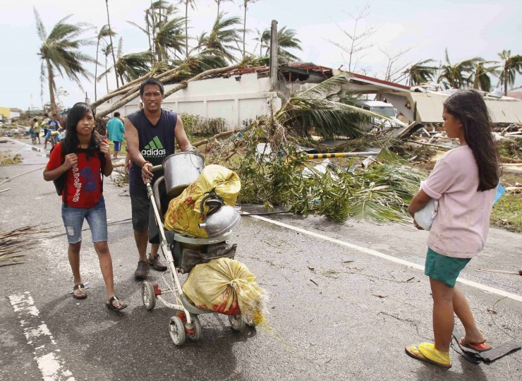 Survivors transport their belongings on a stroller past debris in a damaged town after strong winds brought by super Typhoon Haiyan battered Tacloban city, central Philippines November 9, 2013. Typhoon Haiyan, the strongest typhoon in the world this year and possibly the most powerful ever to hit land battered the central Philippines on Friday, forcing millions of people to flee to safer ground, cutting power lines and blowing apart houses. Haiyan, a category-5 super typhoon, bore down on the northern tip of Cebu Province, a popular tourist destination with the country's second-largest city, after lashing the islands of Leyte and Samar with 275 kph (170 mph) wind gusts and 5-6 meter (15-19 ft) waves. (Romeo Ranoco/REUTERS)
