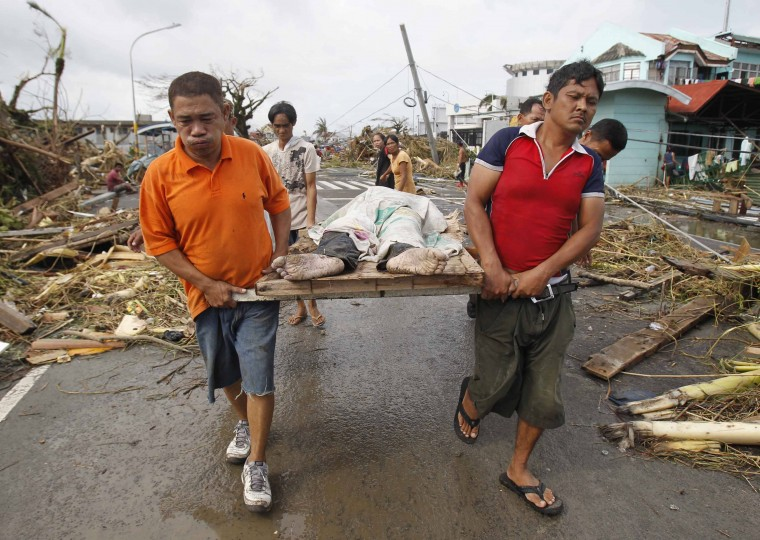 Survivors carry a person killed as super Typhoon Haiyan battered Tacloban city, central Philippines November 9, 2013. Typhoon Haiyan, the strongest typhoon in the world this year and possibly the most powerful ever to hit land battered the central Philippines on Friday, forcing millions of people to flee to safer ground, cutting power lines and blowing apart houses. Haiyan, a category-5 super typhoon, bore down on the northern tip of Cebu Province, a popular tourist destination with the country's second-largest city, after lashing the islands of Leyte and Samar with 275 kph (170 mph) wind gusts and 5-6 meter (15-19 ft) waves. (Romeo Ranoco/REUTERS)