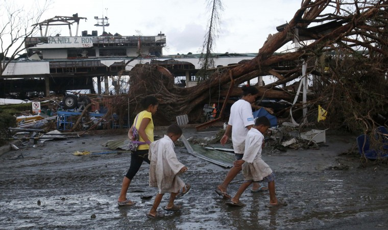 Survivors walk past a fallen tree outside an airport after super Typhoon Haiyan battered Tacloban city, in central Philippines November 9, 2013. Possibly the strongest typhoon ever to hit land devastated the central Philippine city of Tacloban, killing at least 100 people, turning houses into rubble and leveling the airport in a surge of flood water and high wind, officials said on Saturday. The toll of death and damage from Typhoon Haiyan on Friday is expected to rise sharply as rescue workers and soldiers reach areas cut off by the massive, fast-moving storm which weakened to a category 4 on Saturday. (Erik De Castro/REUTERS)