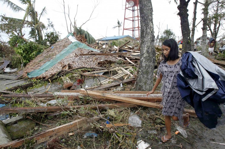 A resident walks past her collapsed house after super Typhoon Haiyan battered Tacloban city, central Philippines, November 9, 2013. Possibly the strongest typhoon ever to hit land devastated the central Philippine city of Tacloban, killing at least 100 people, turning houses into rubble and leveling the airport in a surge of flood water and high wind, officials said on Saturday. The toll of death and damage from Typhoon Haiyan on Friday is expected to rise sharply as rescue workers and soldiers reach areas cut off by the massive, fast-moving storm which weakened to a category 4 on Saturday. (Romeo Ranoco/REUTERS)