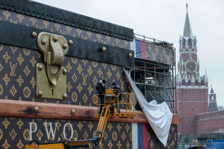 Workers disassemble a Louis Vuitton pavilion shaped like a giant suitcase as Kremlim's Spasskaya Tower is pictured behind in central Moscow November 29, 2013. President Vladimir Putin's government found itself struggling on Wednesday to contain an uproar over the gigantic Louis Vuitton suitcase set up to house an exhibit on the travel and possessions of the rich and famous. (Tatyana Makeyeva/REUTERS)