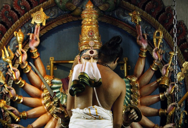 A temple priest adjusts the shield on a Goddess Durga statue at Veeramakaliamman Hindu temple in Singapore October 31, 2013. The Hindu community will celebrate the Festival of Lights known as Diwali or Deepavali, on November 2. (Edgar Su/Reuters)