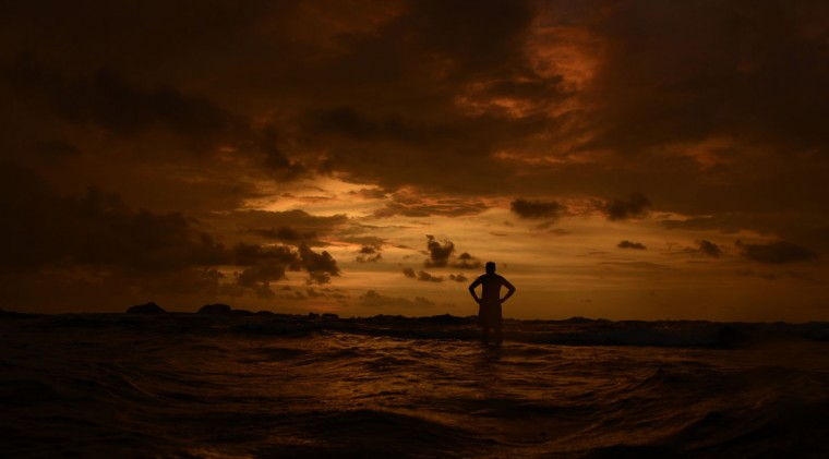A man stands in the sea with his hands on his hips as he watches the sunset in Hikkaduwa November 7, 2013. (Philip Brown/REUTERS)