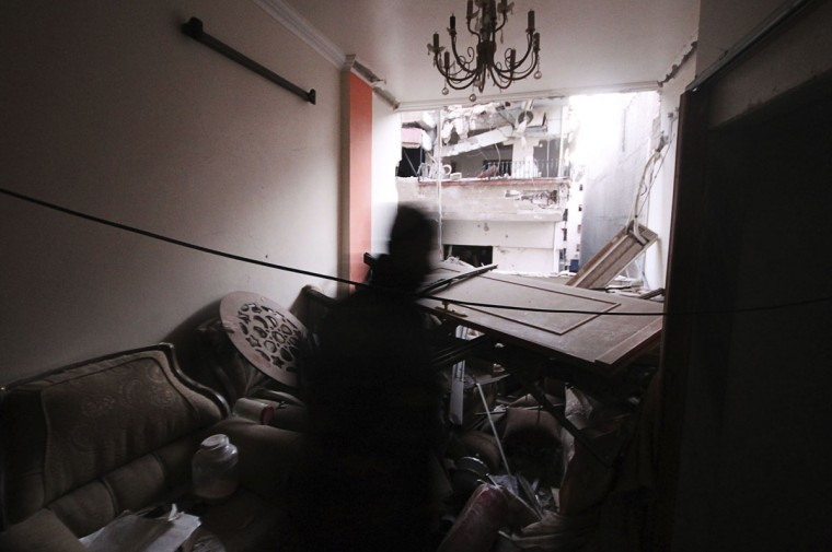 A Free Syrian Army fighter moves inside a damaged house in the Harasta area in eastern al-Ghouta, near Damascus November 22, 2013. (William Ismail/REUTERS)