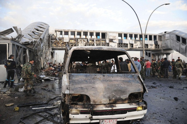 People gather around wreckage after a car bomb at a bus station in Soumariya, near Damascus November 26, 2013, in this handout picture released by Syria's national news agency SANA. Fifteen people were killed and more than 30 were wounded in a suicide bomb attack at a bus station in a suburb west of Damascus, state media said on Tuesday. (Sana/Handout via Reuters)