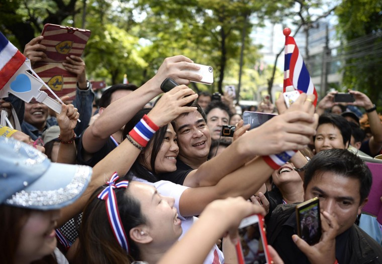 Former Thai Prime Minister Abhisit Vejjajiva is mobbed by supporters during anti-government demonstrations in central Bangkok November 29, 2013. Thousands of protesters took to the streets in the latest escalation in city-wide demonstrations seeking to topple Prime Minister Yingluck Shinawatra. (Dylan Martinez/REUTERS)