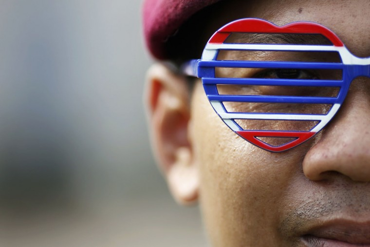 A soldier wears glasses given to him by an anti-government protester who broke in with others into the compound of the Royal Thai Army headquarters in Bangkok November 29, 2013. About 1,500 anti-government protesters forced their way into the compound of Thailand's army headquarters on Friday, the latest escalation in a city-wide demonstration seeking to topple Prime Minister Yingluck Shinawatra. (Damir Sagolj/REUTERS)