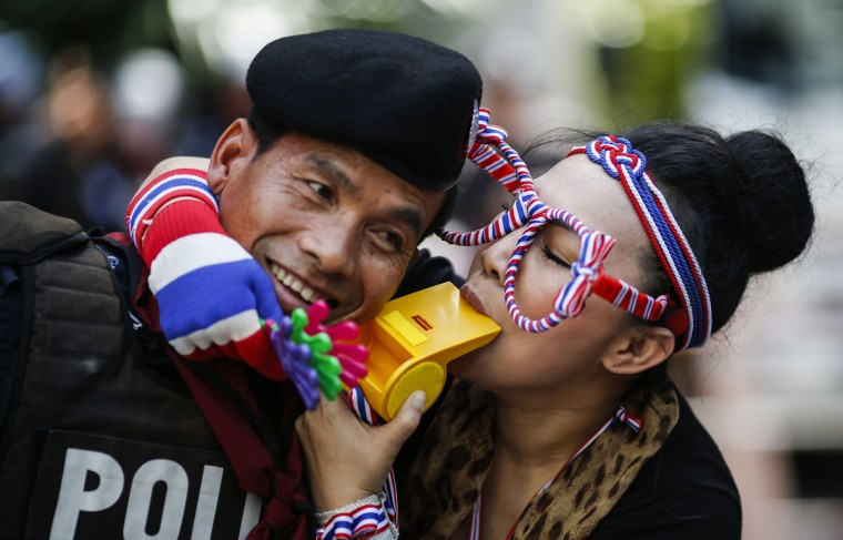 An anti-government protester blows on a whistle next to a riot policeman as she gathers with others outside the headquarters of the ruling Puea Thai Party of Prime Minister Yingluck Shinawatra in Bangkok November 29, 2013. (Athit Perawongmetha/REUTERS)