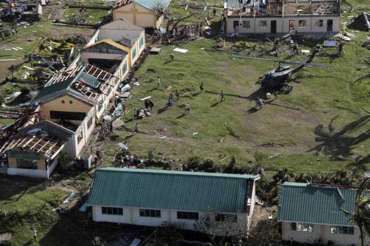 An aerial view shows damaged structures as residents unload relief goods from a helicopter after Typhoon Haiyan hit a village in Panay island in northern Iloilo Province, central Philippines November 9, 2013. Typhoon Haiyan, possibly the strongest storm ever to hit land, has devastated the central Philippine city of Tacloban, killing at least 100 people and destroying most houses in a surge of flood water and high winds, officials said on Saturday. The toll of death and damage is expected to rise sharply as rescue workers and soldiers reach areas cut off by the massive storm, now barrelling out of the Philippines towards Vietnam . (Leo Solinap/REUTERS)