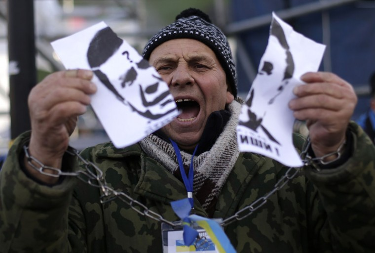 A protester with chained hands tears a portrait of Ukraine's President Viktor Yanukovich during a demonstration in support of EU integration at Independence Square in Kiev November 29, 2013. Ukraine's President Viktor Yanukovich failed on Thursday to salvage an ambitious free-trade pact with the European Union despite a warning that Ukraine was risking its future by turning its back on the deal. Ukraine and the 28-nation EU had aimed to sign an ambitious trade and cooperation agreement at Thursday's summit in the Lithuanian capital Vilnius, which would have marked a historic westwards shift by the former Soviet republic away from Russia's orbit. (Stoyan Nenov/REUTERS)