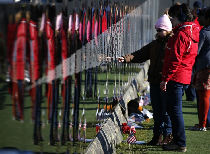 Emma Kearby (L) points to a family name on the Vietnam Moving Wall as her mother Claire looks on during Veterans Day weekend in Aurora, Illinois November 10, 2013. The Moving Wall is a three-fifths replica of the Vietnam Veterans Memorial in Washington D.C. Veterans Day is observed on November 11. (Jeff Haynes /Reuters)