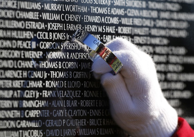 Lisa Roscoe holds a POW bracelet by a name on the Vietnam Moving Wall during Veterans Day weekend in Aurora, Illinois November 10, 2013. The Moving Wall is a three-fifths replica of the Vietnam Veterans Memorial in Washington D.C. Veterans Day is observed on November 11. (Jeff Haynes /Reuters)