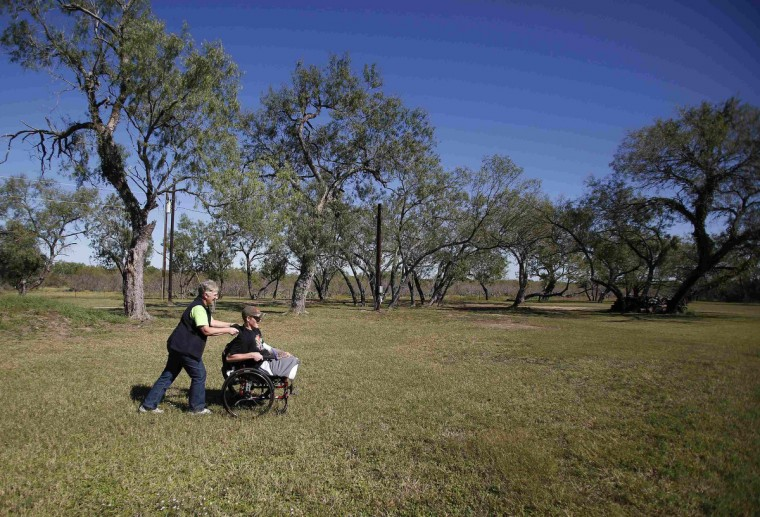 Sgt. Matt Krumwiede of the U.S. Army sits in his wheelchair as he is pushed by his mother Pam Krumwiede at a hunting ranch outside San Antonio, Texas November 3, 2013. (Jim Urquhart/Reuters)