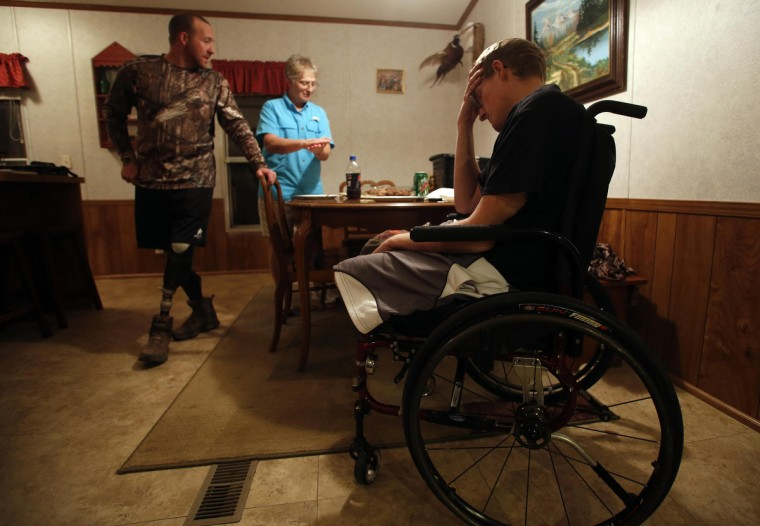 Sgt. Matt Krumwiede of the U.S. Army (R) sits in pain while his friend Sgt. Jesse McCart and his mother Pam Krumwiede talk, after a day of hunting at a ranch outside San Antonio, Texas November 2, 2013. (Jim Urquhart/Reuters)