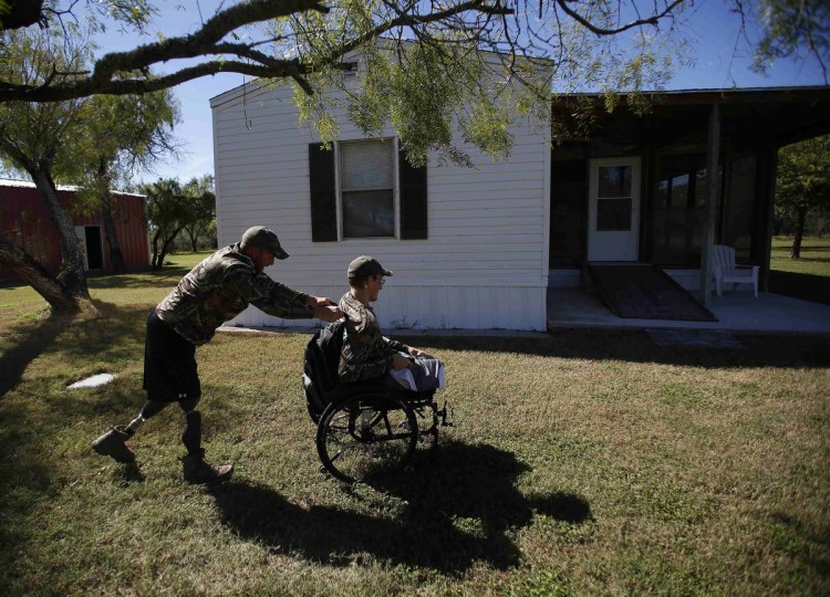 Sgt. Matt Krumwiede of the U.S. Army sits in his wheelchair as he is pushed by his friend Sgt. Jesse McCart at a hunting ranch outside San Antonio, Texas November 3, 2013. (Jim Urquhart/Reuters)