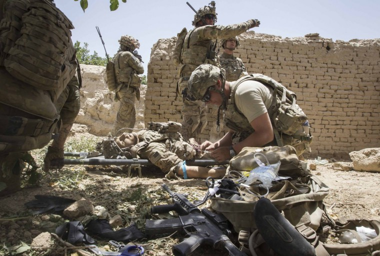 U.S. Army soldiers secure an area, as a medic treats Sgt. Matt Krumwiede who was wounded by an improvised explosive device (IED) in southern Afghanistan June 12, 2012. (Shamil Zhumatov/Reuters)