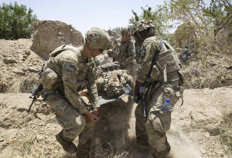 U.S. Army soldiers carry Sgt. Matt Krumwiede, who was wounded by an improvised explosive device (IED), towards a Blackhawk Medevac helicopter in southern Afghanistan June 12, 2012. (Shamil Zhumatov/Reuters)