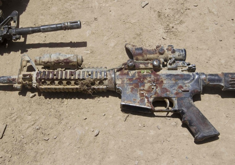 A blood-covered M4 rifle belonging to Sgt. Matt Krumwiede, who was wounded by an improvised explosive device (IED), lies on the ground in southern Afghanistan on June 12, 2012. (Shamil Zhumatov/Reuters)