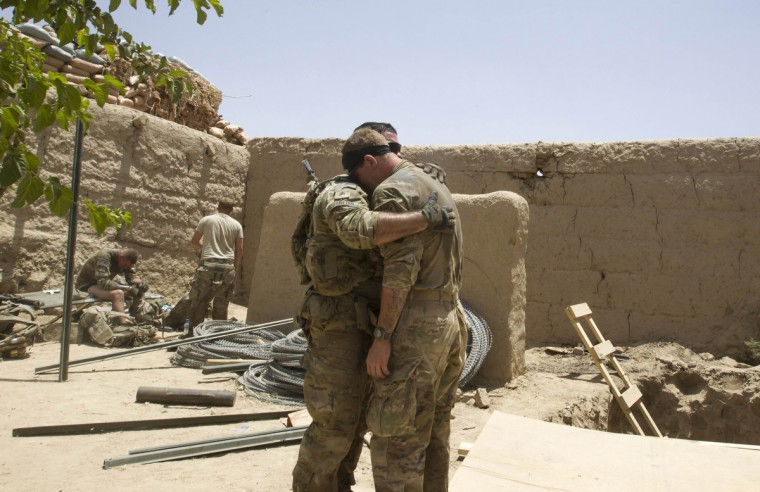 U.S. Army soldiers react after Sgt. Matt Krumwiede was wounded by an improvised explosive device (IED) in southern Afghanistan June 12, 2012. (Shamil Zhumatov/Reuters)