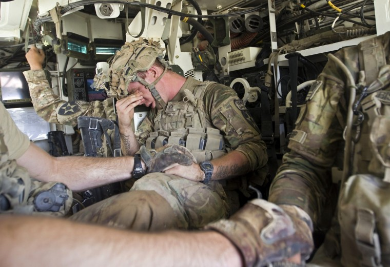 A U.S. Army soldier reacts as he sits inside an armoured vehicle after his comrade, Sgt. Matt Krumwiede, was wounded by an improvised explosive device (IED) in southern Afghanistan. (Shamil Zhumatov/Reuters)