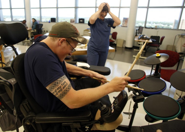 Sgt. Matt Krumwiede of the U.S. Army plays a drumming computer game during occupational therapy at the Center for the Intrepid at Brooke Army Medical Center in San Antonio, Texas August 1, 2013. (Jim Urquhart/Reuters)