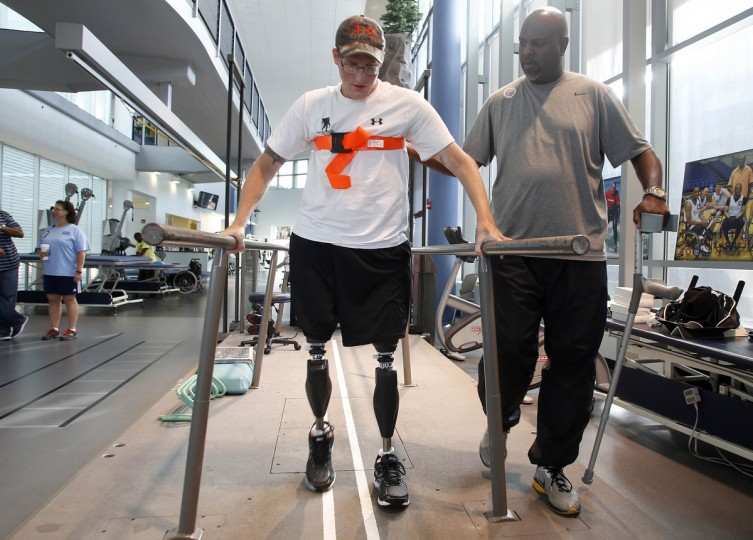 Sgt. Matt Krumwiede of the U.S. Army practices walking with his physical therapist Troy Hopkins at the Center for the Intrepid at Brooke Army Medical Center in San Antonio, Texas August 1, 2013. (Jim Urquhart/Reuters)