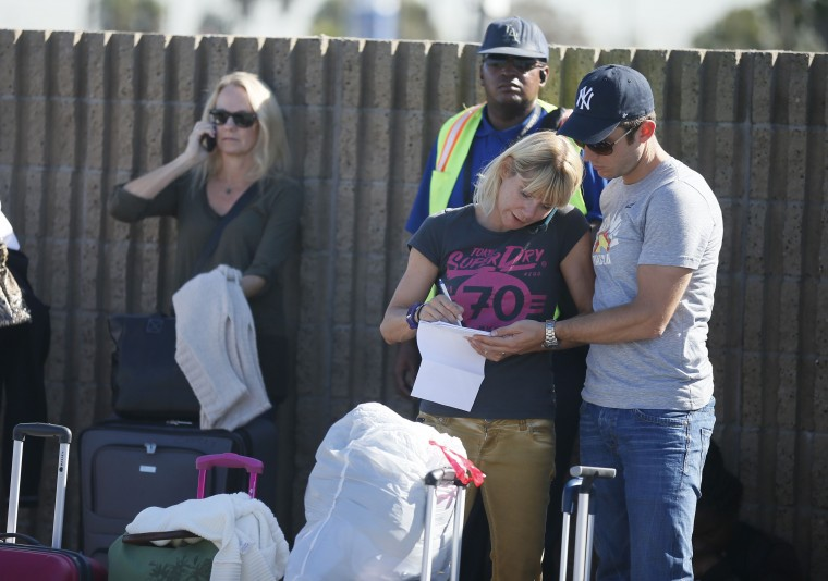 Evacuated passengers wait on a road after a shooting incident at Los Angeles airport (LAX), California November 1, 2013. Several people were injured in a shooting incident that sparked chaos at the Los Angeles International Airport on Friday and authorities said the suspected gunman was in custody. (Lucy Nicholson/Reuters)