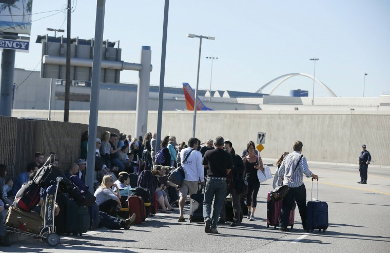 Evacuated passengers wait on a road after a shooting at Los Angeles airport (LAX), California November 1, 2013. (Lucy Nicholson/Reuters)
