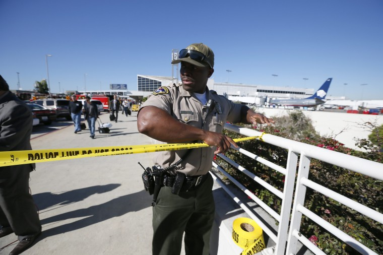 An airport police officer cordons off terminals 2 and 3 after a shooting at Los Angeles airport (LAX), California November 1, 2013. A suspect in a multiple-victim shooting incident at Los Angeles International Airport has been taken into custody and is the only suspect in the incident, a Los Angeles police spokeswoman said on Friday. (Lucy Nicholson/Reuters)