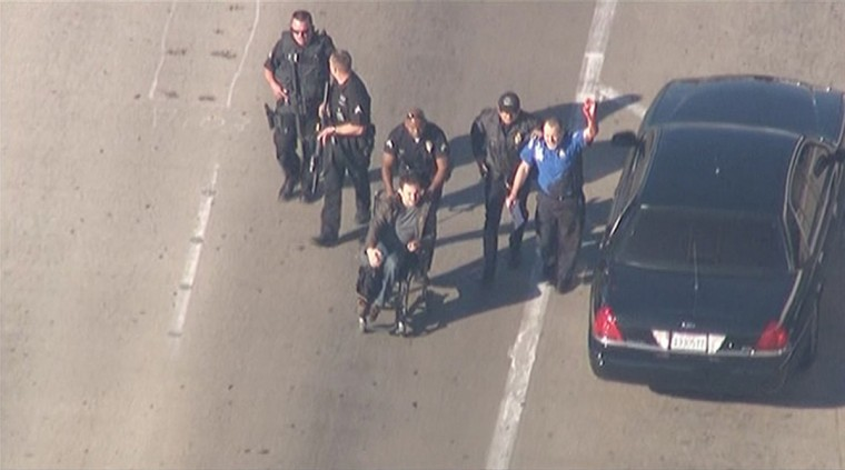 Police escort a man in a wheelchair toward medical help during an incident in which shots were fired at Los Angeles International Airport in Los Angeles in this still image taken from video provided by KNBC November 1, 2013. (KNBC/Reuters)