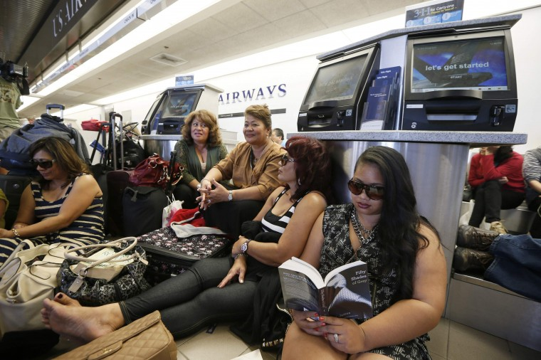 Delayed passengers sit on a baggage conveyer belt after a shooting incident at Los Angeles airport (LAX), California November 1, 2013. (Lucy Nicholson/Reuters)