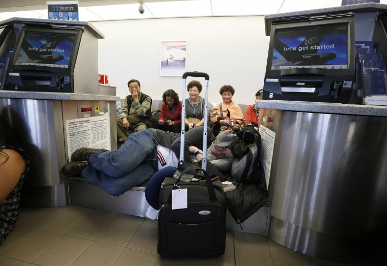 Delayed passengers rest on a baggage conveyer belt after a shooting incident at Los Angeles airport (LAX), California November 1, 2013. (Lucy Nicholson/Reuters)