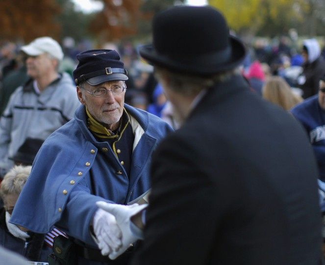A Union soldier (L) Civil War re-enactor shakes hands with a person dressed in civilian Civil War clothes at the Gettysburg National Cemetery in Pennsylvania November 19, 2013. The cemetery is the burial ground for Civil War Union soldiers in which U.S. President Abraham Lincoln travelled to in 1863 to deliver a few concluding remarks at a formal dedication. Today marks the 150th anniversary of Lincoln's famous two-minute speech, the Gettysburg Address. (Gary Cameron/REUTERS)