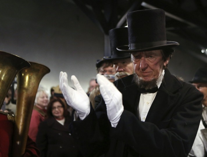 A re-enactor portraying former U.S. President Abraham Lincoln applauds a military band while being welcomed at the Gettysburg, Pennsylvania train station November 18, 2013. Lincoln traveled to Gettysburg in 1863 to deliver a few concluding remarks, his Gettysburg Address, at a formal dedication of the Gettysburg National Cemetery. Tomorrow marks the 150th anniversary of Lincoln's famous two-minute speech. (Gary Cameron/REUTERS)