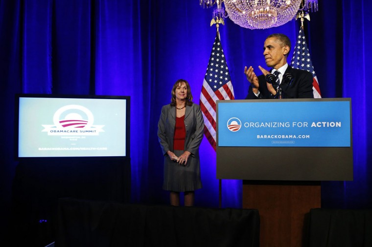 U.S. President Barack Obama (R) applauds after being introduced by volunteer Leslie Sheffield (L) as he takes the stage for remarks on the Affordable Care Act, commonly known as Obamacare, at an Organizing for Action grassroots supporter event in Washington, November 4, 2013. (REUTERS/Jonathan Ernst)